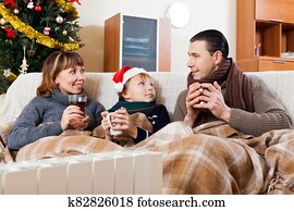 parents and son warming near warm heater