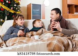 family of three warming near warm radiator