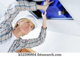 female worker fitting ventilation system in buildings ceiling