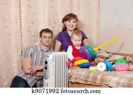 Family at home near oil heater