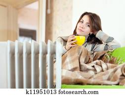 woman near oil heater at home