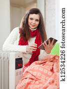 woman reads eBook near warm radiator