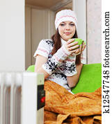 woman relaxing with cup near heater