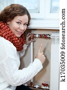 Smiling woman gesturing when turning thermostat on central heating radiator