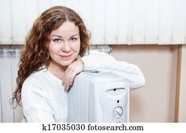 Woman sitting near radiator