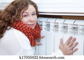 Young woman leaning to central heating convector for warming hands