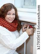 Woman controling the temperature of heating radiator in domestic room