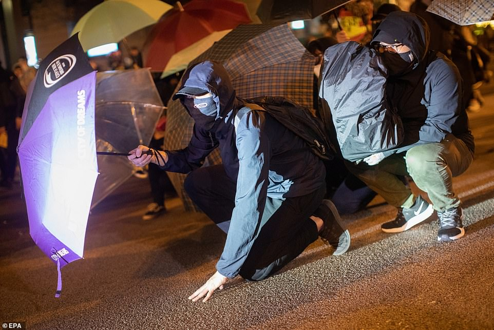 Protesters shield themselves behind umbrellas as Hong King police fire rounds of tear gas at them on Christmas Eve