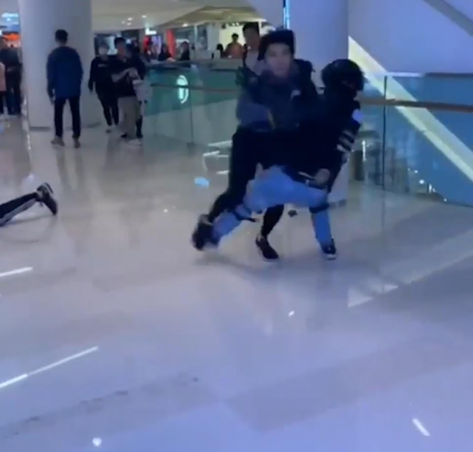 The man pushes passed an officer and  sprints across the second floor of Yuen Long mall in Hong Kong on Christmas Eve