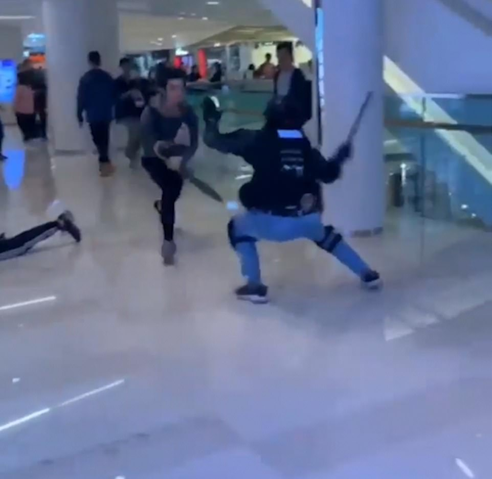 The unidentified protester runs across the second floor of a mall in an effort to escape Hong Kong police on Christmas Eve