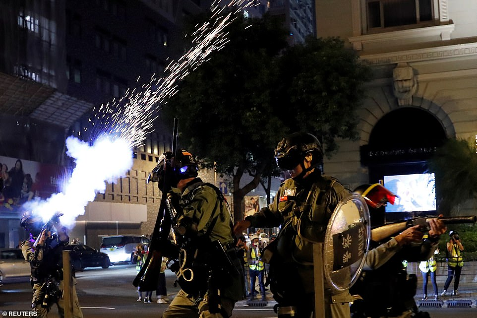 Hong Kong riot police officers stand on guard and fire shots of tear gas at anti-government protesters on the city streets