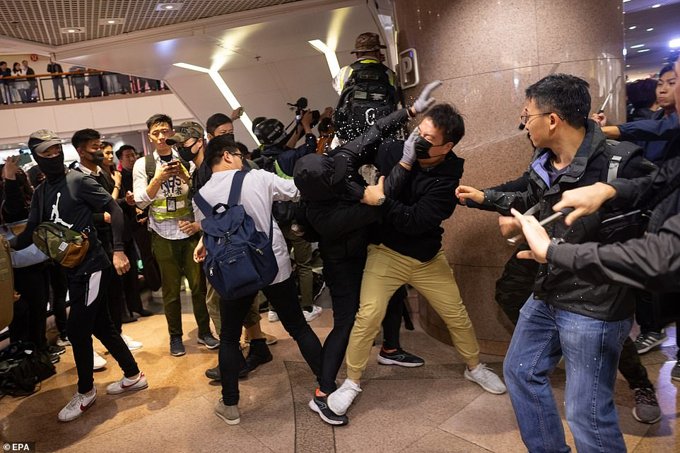 Plain clothed police officers clash with pro-democracy protesters in a shopping mall in Hong Kong on Christmas Eve