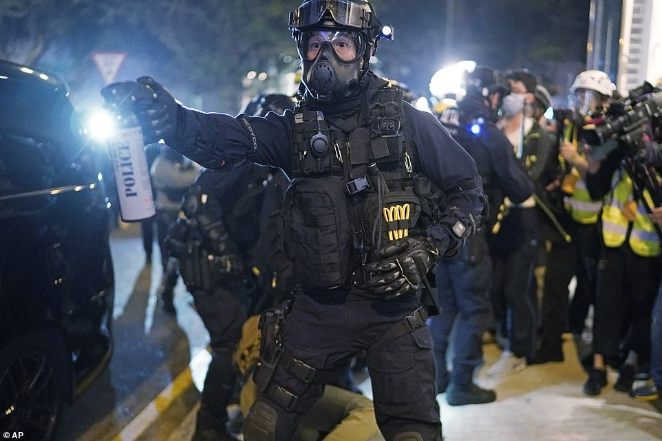 An officer wearing a gas mask and protective clothing gestures to a crowd to clear the street as hundreds continue to rally against the government