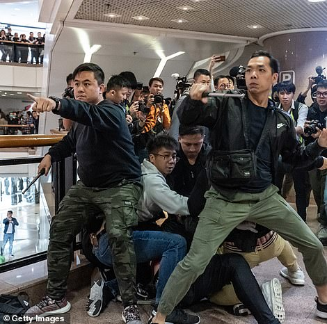 Officers dressed in plain clothes clash with the tide of Hong Kong protesters inside a shopping mall on the eve of Christmas