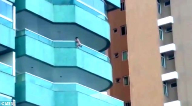 The three-year-old appeared to be clinging on to the fifth floor balcony of a block of flats in Brazil