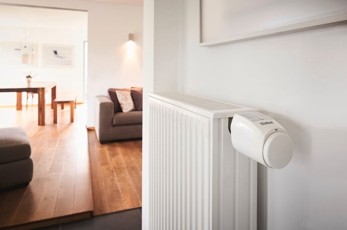 A radiator with the Vaillant ambiSENSE smart TRV in the hall of a modern home.